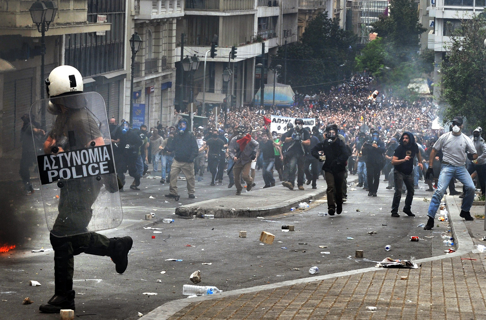 A Greek riot police officer runs to esca